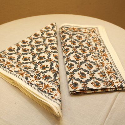 Cotton block-print napkin. Traditional indian pattern with orange flower on white cotton.