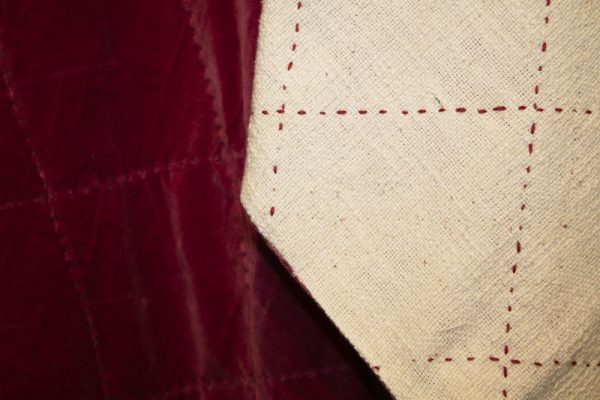 Quilted cotton velvet throw in garnet red. Cream reverse with garnet stitching.